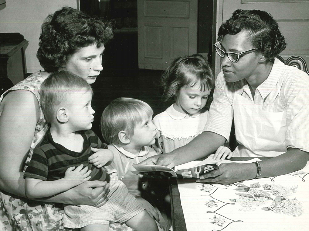 Two members of the Visiting Nurses' Association read a book to three small children