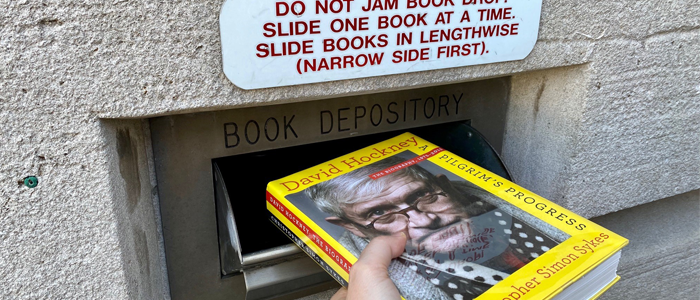 Close-up of someone using Hillman Library's bookdrop