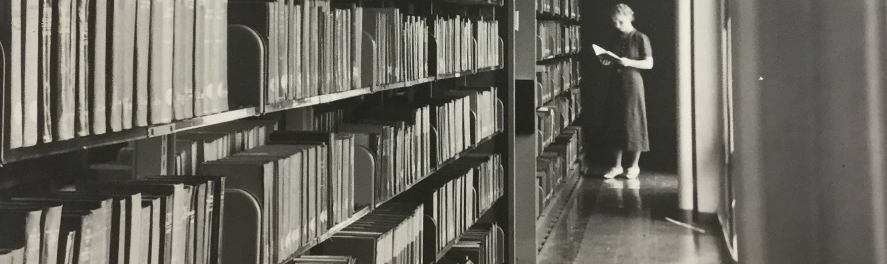 Lady looking through a book, with bookshelves in the foreground. Circa 1950.