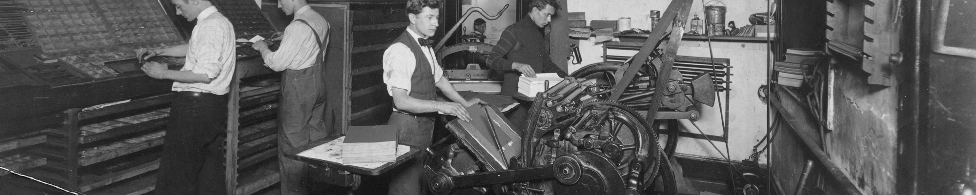 Two men are setting type and two men are operating platen printing presses in 1925