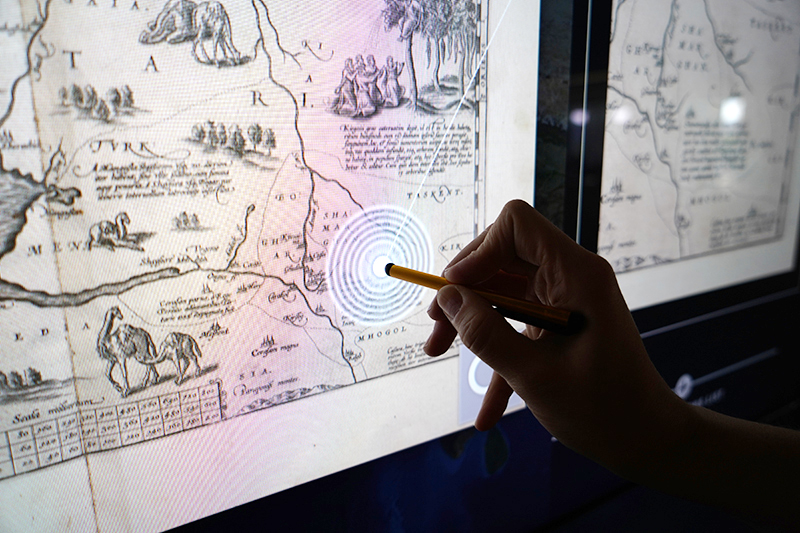 Close up of someone using a stylus on the interactive wall